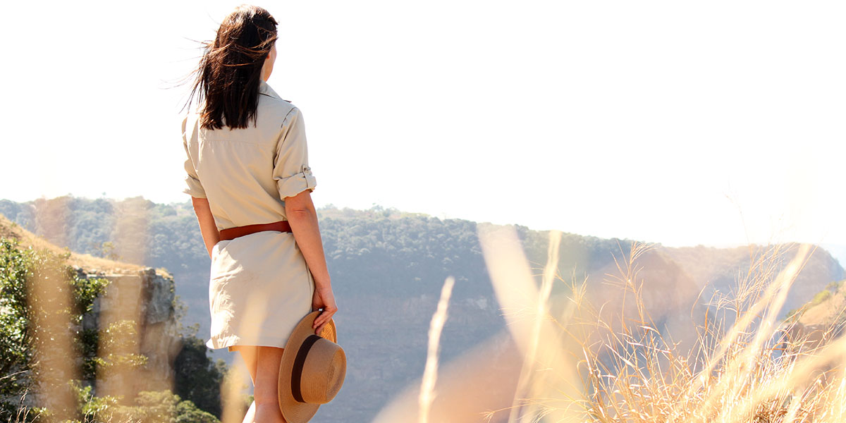 Woman wearing a safari dress in technical fabric in long grass looking out over a gorge, with a safari panama hat in her hand