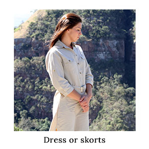 Woman standing with forested cliffs behind her wearing a safari dress made from protective technical fabric for outdoor style