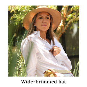 Woman in a white travel shirt and a wide-brimmed panama hat for sun protection and outdoor style on a blue safari