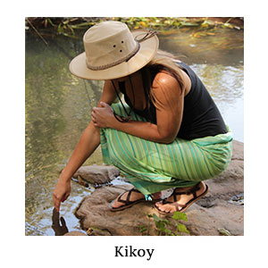 Woman in a safari hat, black top, and green striped, Kenyan-made kikoy bending down to touch the river on a blue safari