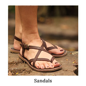 A woman's feet in brown leather safari sandals standing on a rock for outdoor and safari style on a blue safari