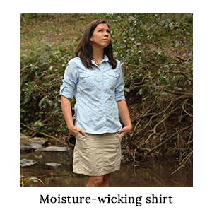 Woman in an insect protective blue travel and outdoor shirt and safari skorts in the bush next to a river on a blue safari