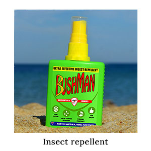 DEET-based, Australian-made Bushman Pump Spray bug repellent in the sand on the beach for insect protection on a blue safari