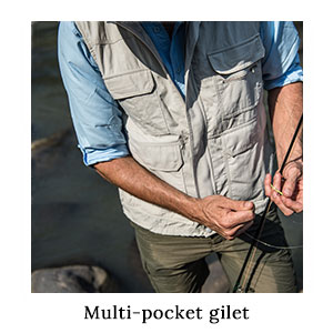 Fisherman with a rod adjusting his line in outdoor clothing and a multi-pocket gilet in technical fabric as a fishing vest