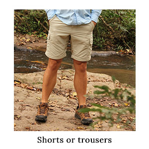 Man's legs on a rock next to a river in a pair of safari zip-off trousers which have been converted into outdoor shorts