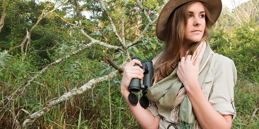 A woman in safari and travel clothing holding a pair of Vortex binoculars