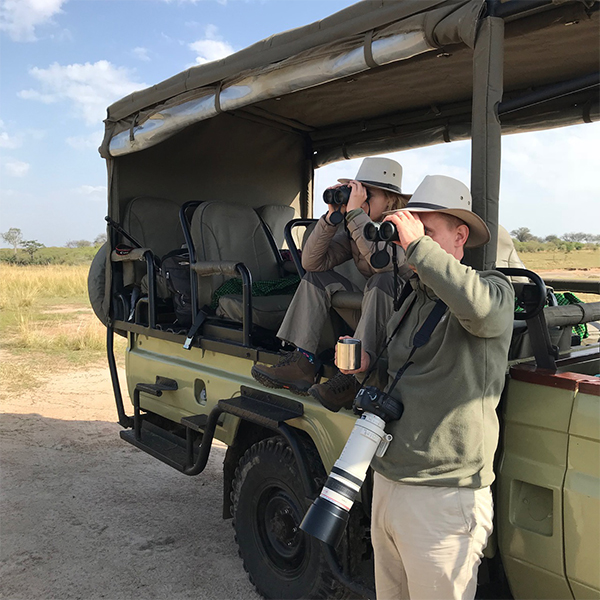 Sean from London using our rental binoculars on safari in Tanzania, 2018