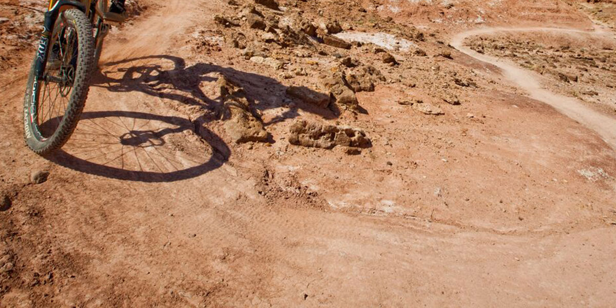 The front tyre of a mountain bike with the shadow of a cyclist riding on a winding dirt trail on a cycle safari in Africa
