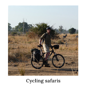 A man in safari clothing standing with his bicycle on an expedition tested trip to Luangwa in Zambia on a cycling safari
