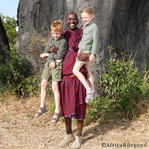 A smiling Masai man in a traditional red shuka holds a boy and girl wearing safari clothing while on holiday in Kenya