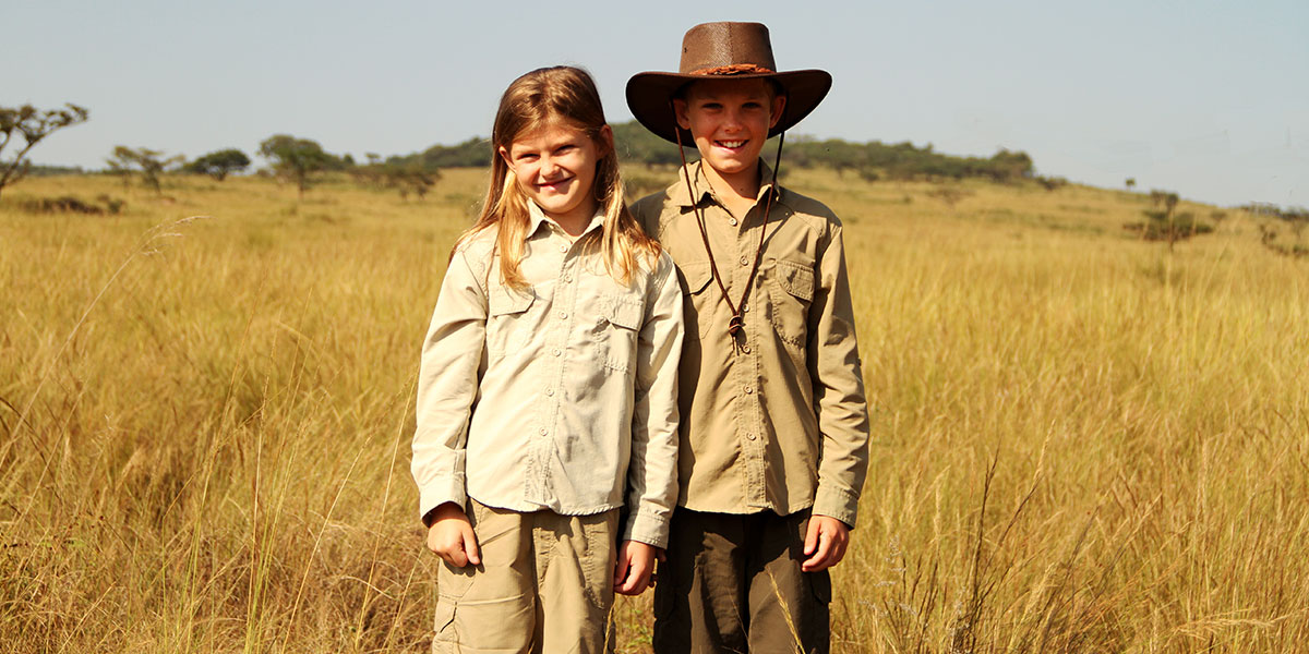 Two smiling children, a boy and girl, standing in brown savannah grass wearing safari clothing and a hat