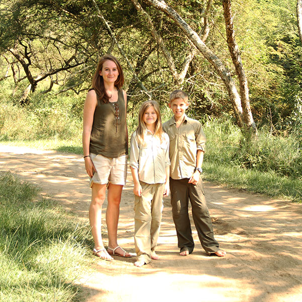 A smiling woman and two children, a boy and girl, in safari clothing standing on a dirt road surrounded by trees