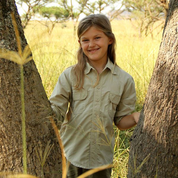 A smiling young girl standing between two trees wearing safari clothing
