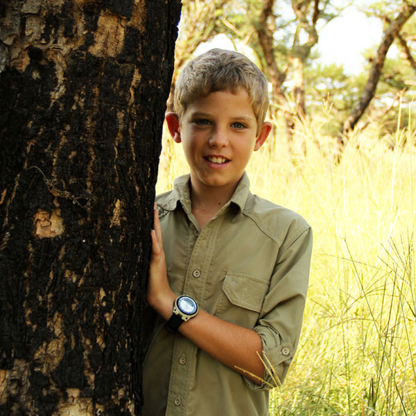 A young boy standing next to a tree wearing a watch and a safari shirt