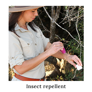 A woman in safari clothing applying Australian-made, DEET-based insect repellent on her arm for insect protection on safari