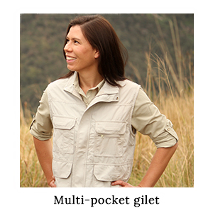 A woman standing in long grass wearing a safari shirt and a gilet with many pockets in ripstop technical fabric on safari