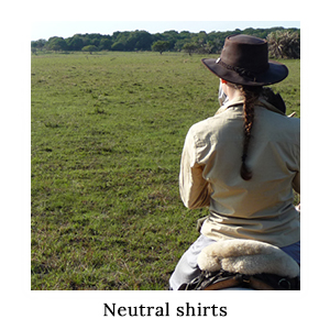 A woman in a neutral-coloured safari shirt in ripstop technical fabric on horseback on a plain on a horse safari in St Lucia