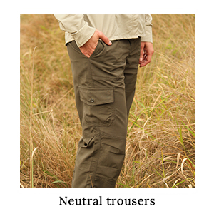 A woman with her hand in the pocket of her safari trousers in ripstop technical fabric in long grass on safari in Africa