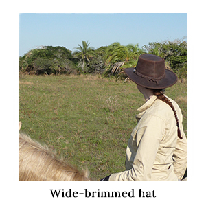 A woman in a safari shirt on horseback wearing a leather wide-brimmed hat for sun protection on a horse safari in St Lucia
