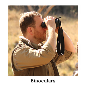 A man in safari clothing game-viewing or bird-watching through a pair of binoculars on safari in Africa