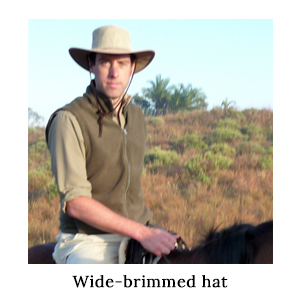 A man on horseback wearing safari clothing and a wide-brimmed hat for sun protection on a horse safari in St Lucia