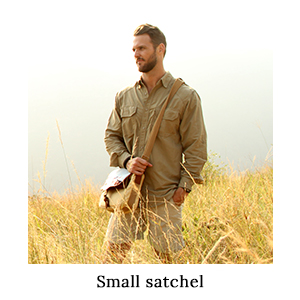 Man standing in long grass wearing safari clothing and carrying a small satchel with the strap across his chest on safari