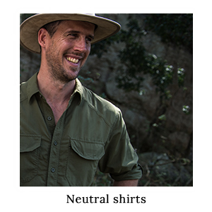 A man in a safari-friendly, neutral shirt made from insect repellent fabric and a safari hat on safari in Africa