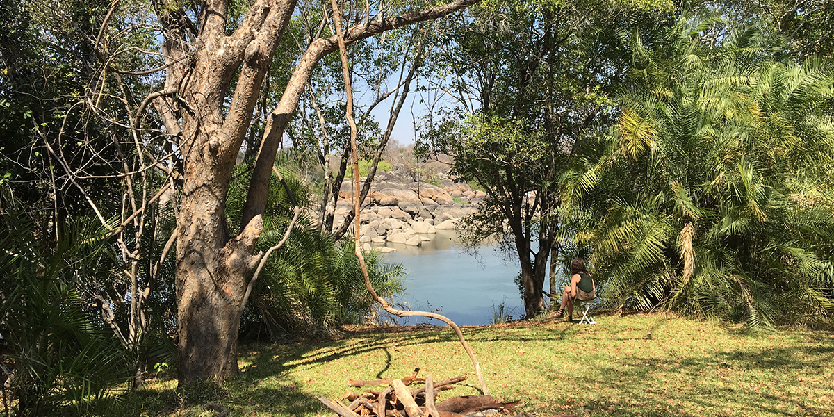 A woman wearing safari clothing sitting next to the rocky Kafue river in Zambia writes in her journal
