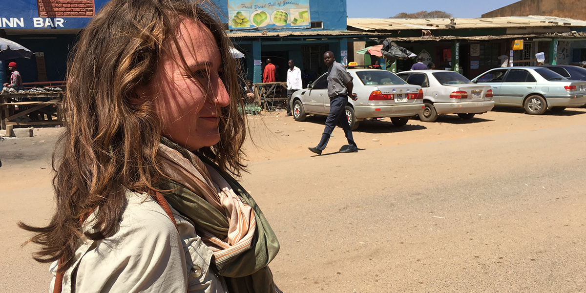 A close-up of a woman wearing a scarf on the dusty street of Mumbwa in Zambia. There are cars, shops and people in the background