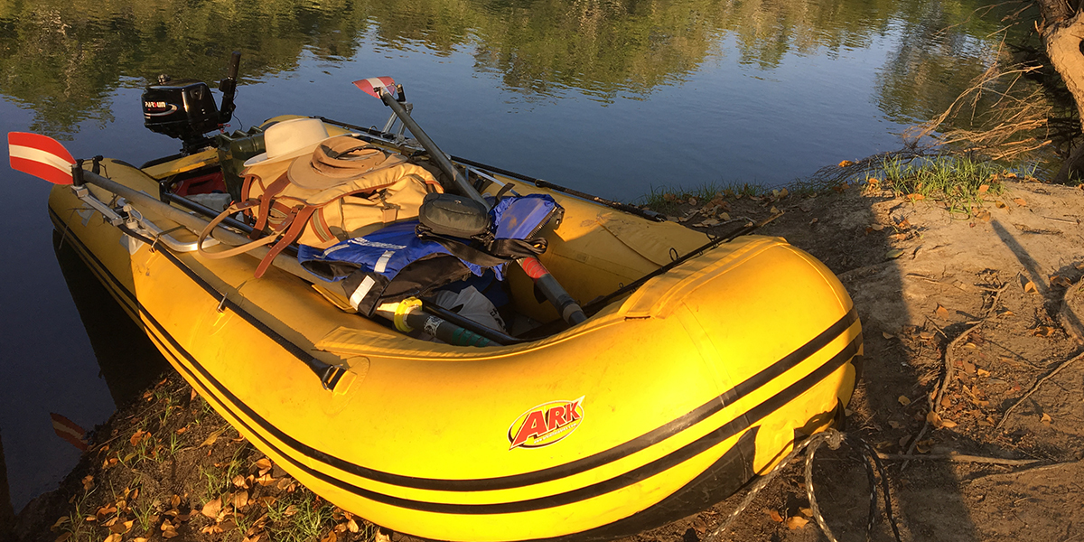 A yellow inflatable boat on the shore of the Kafue river in Zambia. Inside the boat is luggage, hats and other safari gear