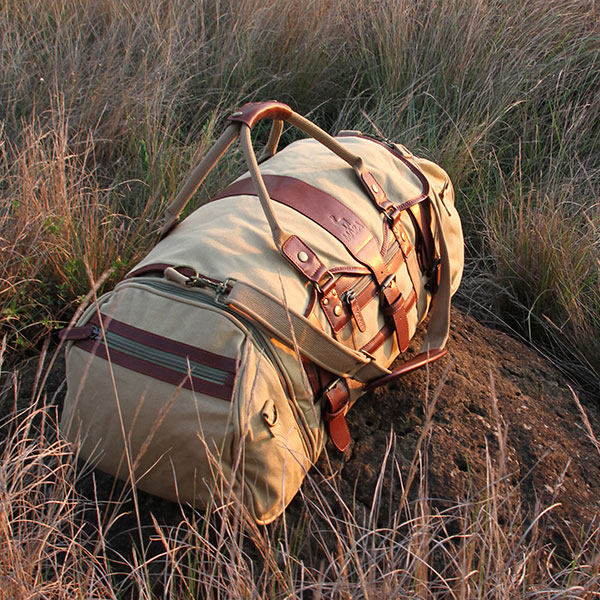 A luxury tan canvas and leather duffel bag on top of a rock surrounded by savanna grass.