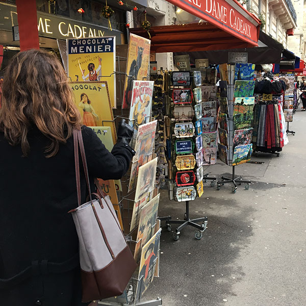 A woman in a black coat carrying a canvas tote bag looks at souvenirs in France