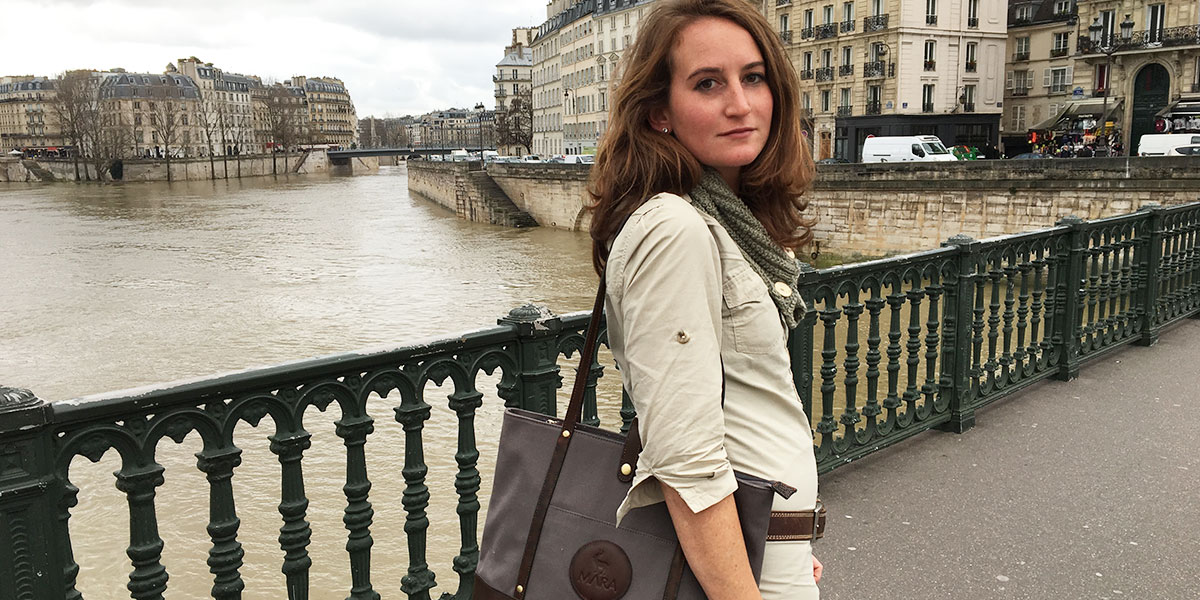 A woman travelling in France carrying a canvas and leather tote bag. A river and some buildings are in the background.