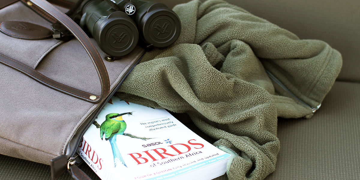 A green fleece and South African bird book in a canvas and leather tote bag.