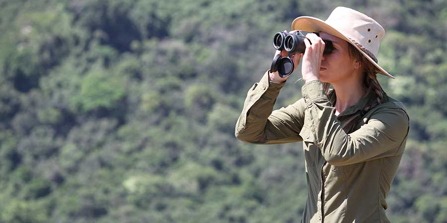 A woman in safari clothing looking through binoculars