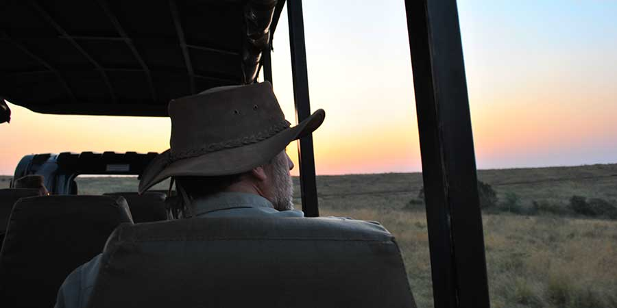 A man wearing a hat on a game drive in Africa at sunset
