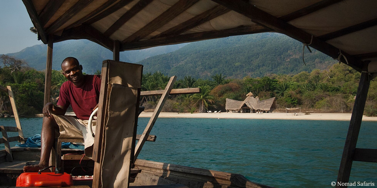 A smiling man in a red shirt on a boat going towards a mountainous island in Mahale, Tanzania