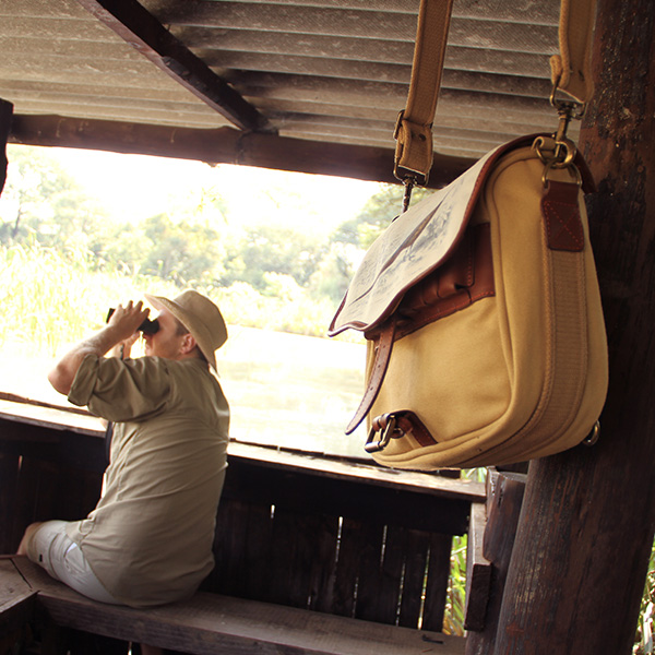 A man in a hat looking through binoculars. A leather and canvas satchel hangs from a wooden pole.