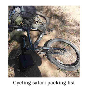 A loaded mountain bike packed with essential gear lying on its side on a dirt trail on a cycle safari in Africa