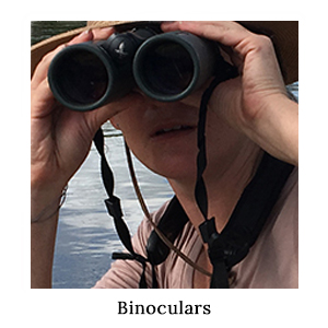 Woman looking through high-quality Swarovski 10x42 binoculars for game-viewing and bird-watching on a paddling safari