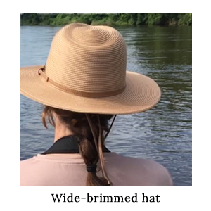 A woman in a wide-brimmed safari hat viewed from behind looking out over a river on a paddling safari on a boat in Africa