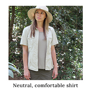 A woman in a hat wearing safari shirts and clothing in neutral colours and made from protective technical fabric on safari
