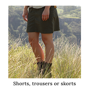 A woman standing in long grass wearing a pair of safari skorts made from protective technical fabric on safari in Africa