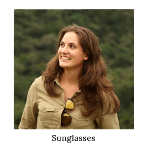 A woman with her Bolle sunglasses hooked between the buttons of her safari shirt for sun protection on safari in Africa