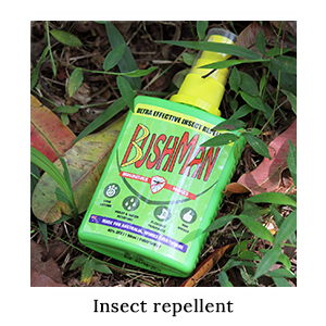 A bottle of Australian-made Bushman Pump Spray insect repellent lying in the grass and leaves on a paddling safari in Africa