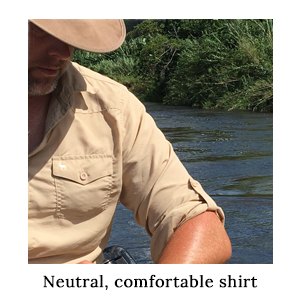 A man in a safari hat and insect protective safari shirt in a neutral colour on a paddling safari in Africa