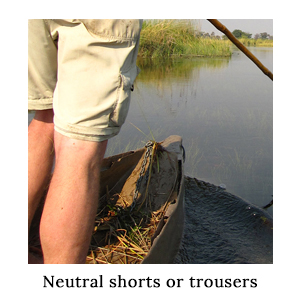 A man's legs standing in a mekoro wearing safari zip-off trousers which have been converted into shorts on a paddling safari