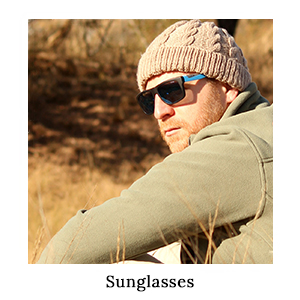 Man in safari clothing sitting in the grass wearing a pair of Bolle sunglasses for sun protection on safari in Africa