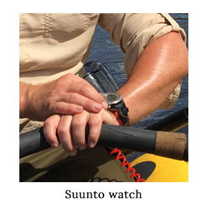 A man in a safari shirt looking at his Suunto fitness GPS watch with a pair of rowing skulls in his hand on a paddling safari