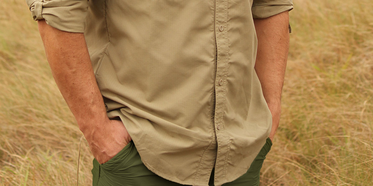 A man dressed in safari clothing with his hands in his pockets